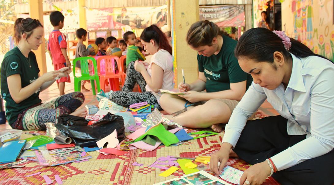 Voluntarias sociales ayudando al personal a crear recursos didácticos.